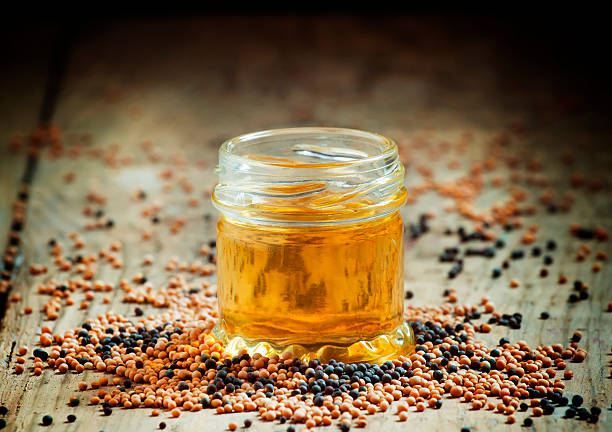 Oil of mustard in a small jar and yellow and black mustard seeds on an old wooden table in rustic style, selective focus